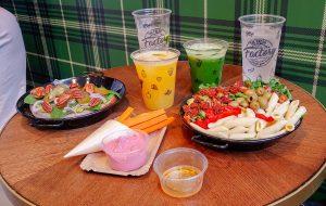 Tafel met eten bietenhummus salade met pasta luxe brood verse sinaasappelsap water en komkommersap