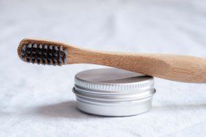 Houten tandenborstel met zilverkleurig blikje