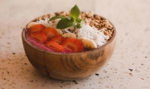 Smoothie bowl in een houten kommetje op een aanrecht