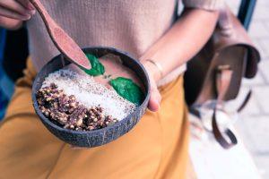 Vrouw houdt een kom met smoothie bowl vast