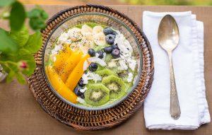Groen en gele smoothie bowl met een zilverkleurige lepel ernaast